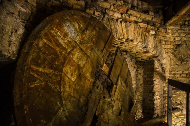Tamsiame kampelyje liūdi senas varpinės laikrodžio ciferblatas
